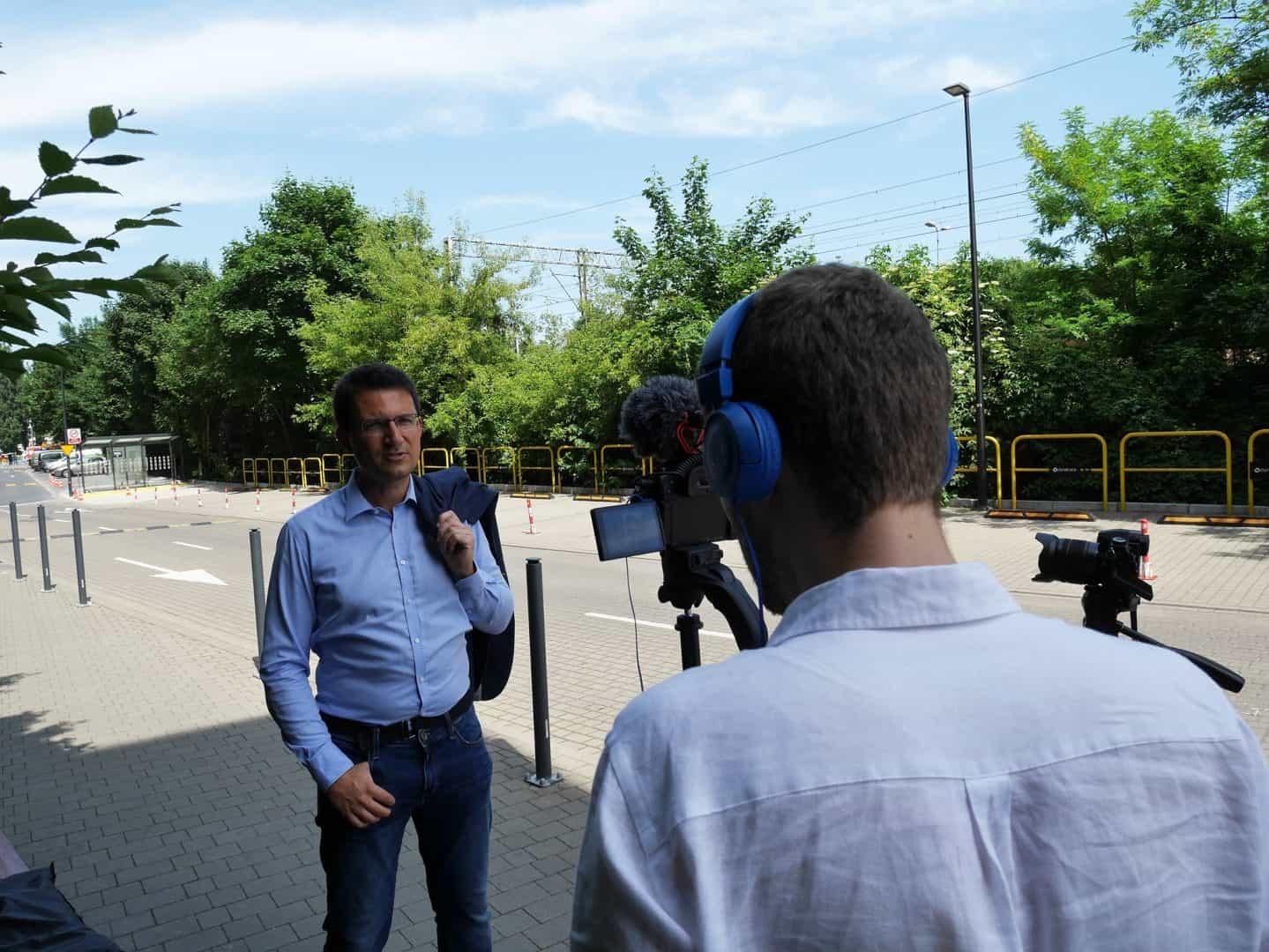 Na pierwszym planie znajduje się operator kamery, który nagrywa osobę opowiadającą o nowej aplikacji. Postacie stoją na chodniku pośród drzew